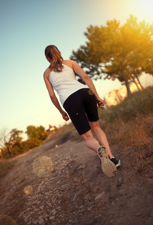 jogger: Jogger woman running on forest trail Stock Photo