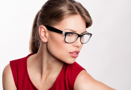 Young stylish girl in optical glasses posing in studio  Smart and beautiful Caucasian woman model wearing spectacles
