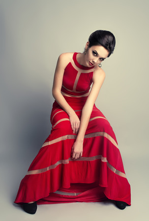 evening dress: Pretty brunette woman in long evening red dress Stock Photo