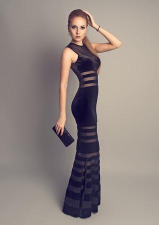 스튜디오에서 검은 우아한 옷 포즈 클러치 패션 숙녀를 들고 세련된 이브닝 드레스를 입고 아름 다운 슬림 모델