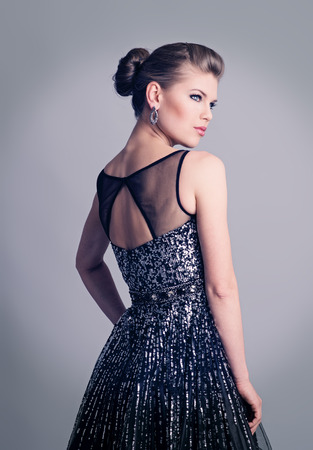 evening dress: Portrait of beautiful fashion woman in luxury glossy dress  Young attractive Caucasian female model wearing expensive stylish clothing and earrings, with evening hairstyle and professional makeup