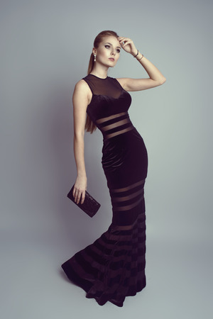 Elegant blonde in luxury black dress holding a handbag   Young pretty Caucasian woman model wearing stylish evening clothes, high heels and pearl earrings  photo