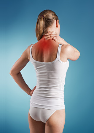 Woman suffer from neck pain, over blue background  Portrait of young girl touching her sick nape  Stock Photo