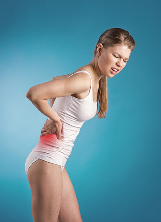 Stressed young woman with back pain photo