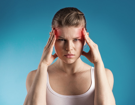 dizziness: Young woman suffer from dizziness or vertigo holding her head  Portrait of exhausted female with migraine problem over blue background