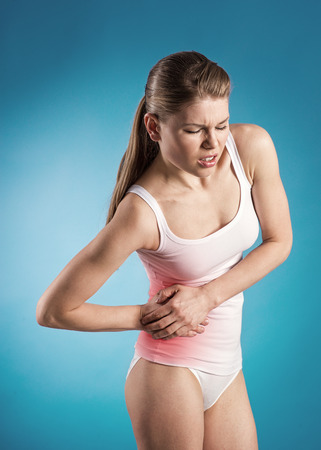 Acute abdominal pain  Young woman with pancreas pain over blue background