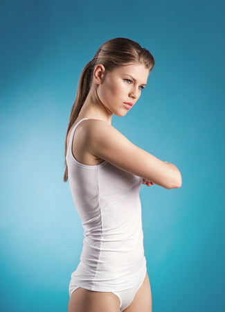 warming therapy: Physical treatment  Young girl doing exercise on painful back over blue background