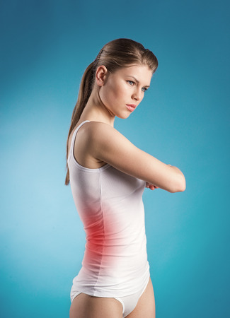 Portrait of woman suffering from liver ache over blue background  Young Caucasian female with pain indicated by red spot  Stock Photo - 27020825
