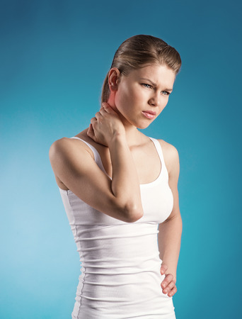 nervios: Localización lesiones Estiramiento del cuello de la chica joven con dolor agudo en la espalda sobre fondo azul con una mancha roja que indica