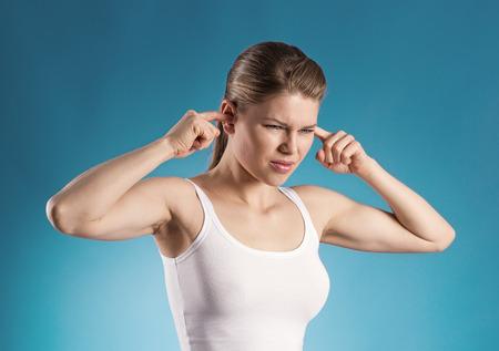 dolor de oido: Retrato de muchacha joven que tiene o�dos problemas sobre fondo azul Atractiva hembra de cauc�sicas cerrando los o�dos del ruido