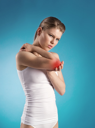 elbow pain: Portrait of female suffering from arthritis and massaging her painful elbow  Tendon inflammation  Stock Photo