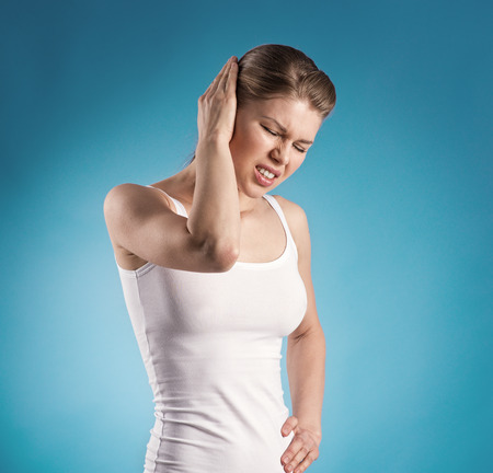 파란색 배경 위에 귀 통증에서 젊은 여성의 고통 스톡 콘텐츠