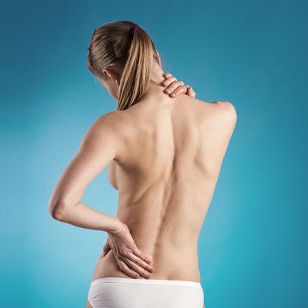 mujer desnuda de espalda: Primer plano de la mujer con la espalda desnuda sufrimiento de dolor de espalda sobre fondo azul
