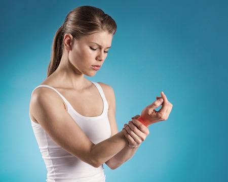 artritis: Joven mujer con su doloroso de la muñeca sobre fondo azul la localización del dolor del esguince indicado por mancha roja