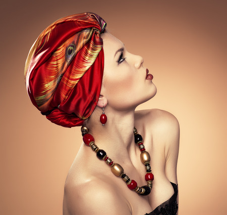 turban: Portrait of ethnic dresses fashionable woman wearing jewelery  Young beautiful Caucasian female model with red turban looking up