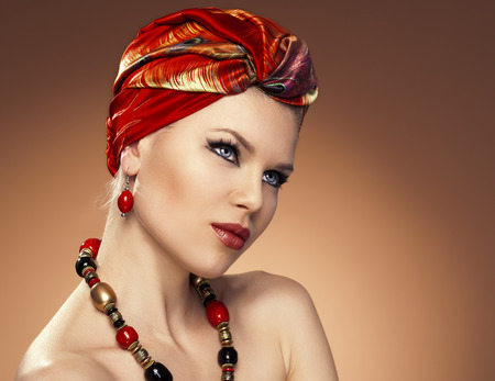 turban: Beauty fashionable woman with hairs wrapped in turban  Pretty Caucasian model wearing red earrings and necklace posing in studio  Stock Photo