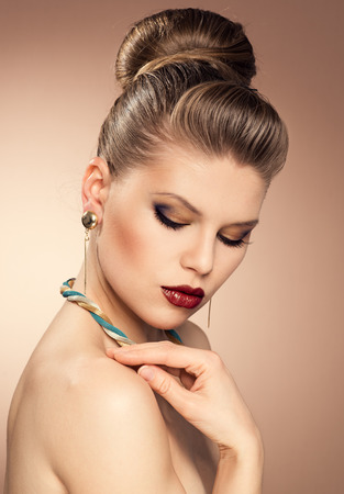 coloring lips: Close-up portrait of fashionable lady wearing luxury golden jewelery with professional make-up and beautiful hairstyle  Young attractive Caucasian woman model posing in studio