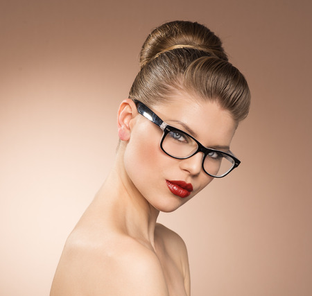 Studio shot of young beautiful lady in glasses looking at camera  Vintage style female portrait  photo