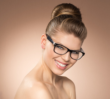 Young stylish attractive girl in optical glasses posing in studio  Smiling and beautiful caucasian female model wearing spectacles  Stock Photo