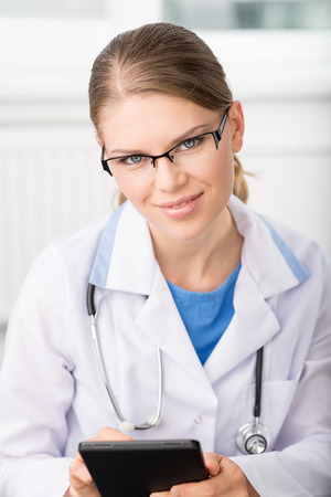Pretty woman physician in eyeglasses with i pad in hospital Stock Photo - 27465760