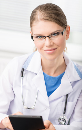 i pad: Young female doctor holding pc tablet sitting at her desk  Portrait of woman therapist touching i pad