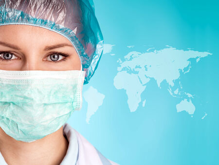 surgical coat: Attractive female doctor in surgical mask and cap over world map background  Close-up portrait of pretty woman surgeon wearing medical uniform