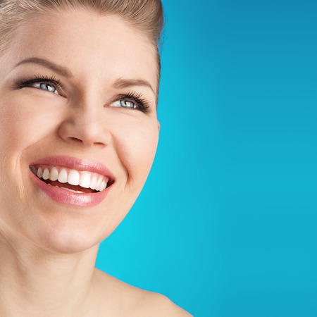 tooth ache: Perfect white toothy smile  Close-up portrait of dental care woman over blue background  Stock Photo
