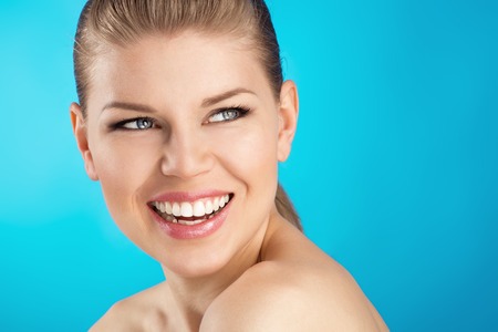 Close-up of beautiful blue eyed woman showing her healthy white teeth  Young attractive Caucasian female model with wide perfect smile over blue background