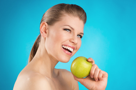 Young woman s portrait with great healthy smile holding green apple  Dental care, teeth protection concept  photo