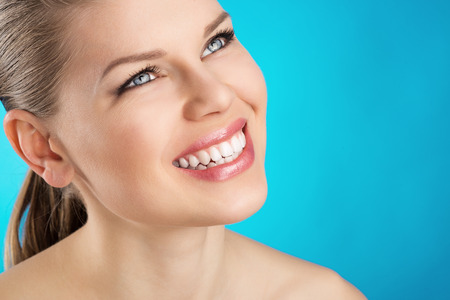 dentition: Teeth cure and whitening  Portrait of beauty woman with healthy toothy smile over blue background