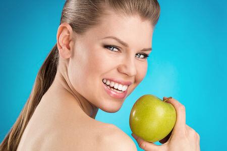 dentier: Protection de la santé des dents Jeune femme modèle assez frais tenant la pomme verte montrant ses dents blanches