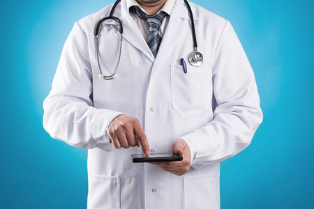 Male doctor using tablet computer for research at work  Young modern practitioner holding electronic device over blue background  photo