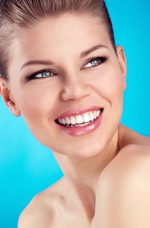 파란색 배경 위에 넓은 완벽한 미소로 젊은 매력적인 백인 여성 모델