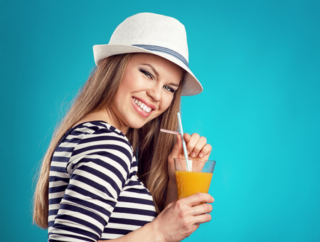 Active fresh summer girl drinking orange juice over blue photo