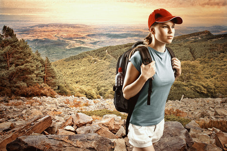 Young woman climber wearing cap with backpack hiking in mountain and hills  Satisfied female traveler in sportswear trekking on sunset  Stock Photo