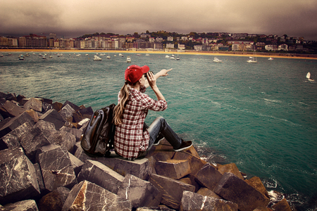 Woman traveler sitting on the stones looking in binocular at horizon  Young female climber with backpack over ocean port background