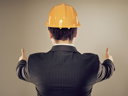 Portrait of male engineer in yellow helmet showing thumbs up  Young successful construction manager posing in studio  photo