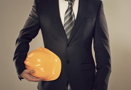 Portrait of male construction director standing with yellow helmet  Young man architect with protective tool  photo