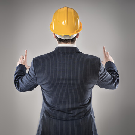 Man architect in hardhat showing, pointing at copy space photo