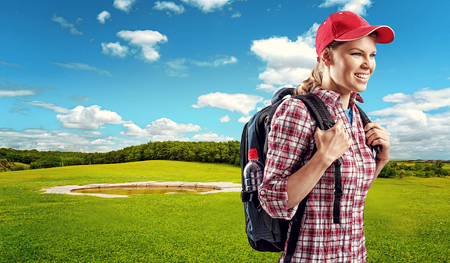Happy female traveler hiking on green field. Young woman trekker with backpack walking through golf park. photo