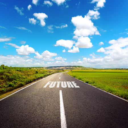 future: A road to future. Beautiful landscape of highway through meadow and white clouds. Stock Photo