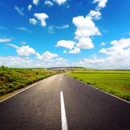 Concept van het rechte pad naar succes. Asfalt weg over blauwe hemel achtergrond. Stockfoto