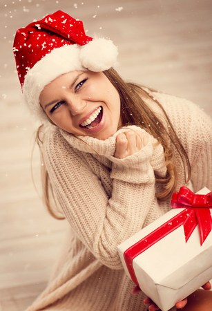 Portrait of beautiful Santa woman enjoying Christmas gift looking snow photo