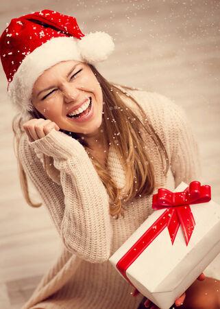 Xmas party celebration. Laughing Santa girl holding white present box with red ribbon enjoying falling snowflakes. photo