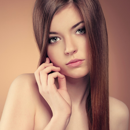 Close-up studio portrait of pretty girl with beautiful healthy long hair. Young pure woman touching her perfect skin.