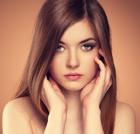 Hair and skin care. Close-up portrait of beautiful sensual young woman touching her pure face.