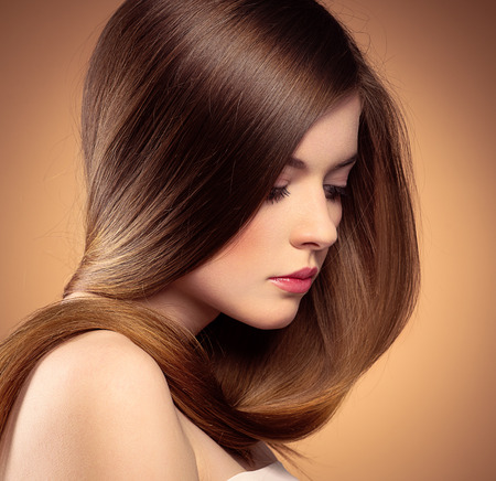 Close-up portrait of beautiful Caucasian teenage girl with healthy straight long hair posing in studio.