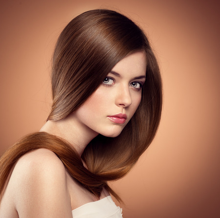 Gentle teenage girl showing her healthy long straight hair. Beautiful Caucasian female model with perfect glossy hair posing in studio. Stock Photo