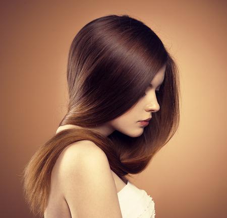 lang haar: Close-up portret van jonge model met glanzende rechte bruin haar. Haarverzorging en kleurstoffen.