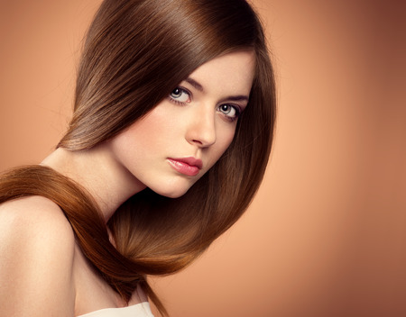 hair style: Beauty salon model with perfect long glossy brown hair posing in studio. Close-up portrait of lovely teenage girl with beautiful hairstyle. Stock Photo